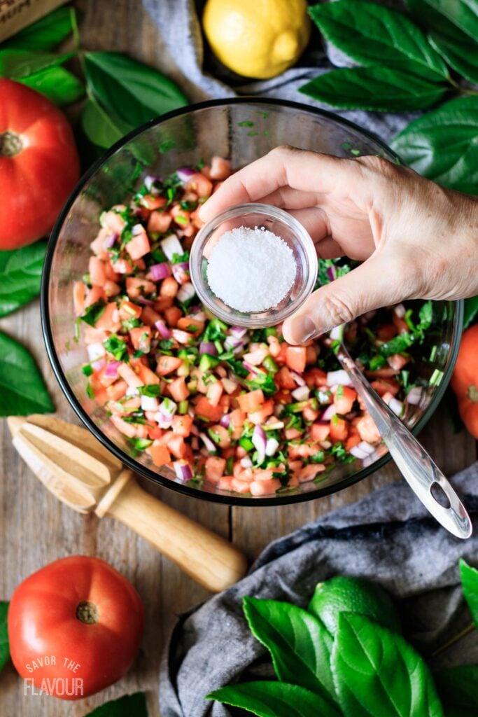 person adding kosher salt to a bowl of tomato salsa
