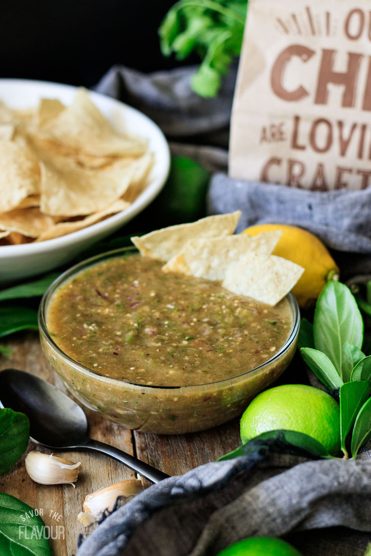 bowl of Chipotle tomatillo green salsa with a spoon and tortilla chips