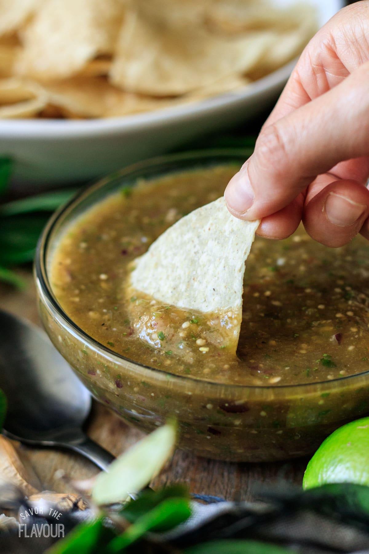 person dipping a tortilla chip into Chipotle tomatillo green salsa
