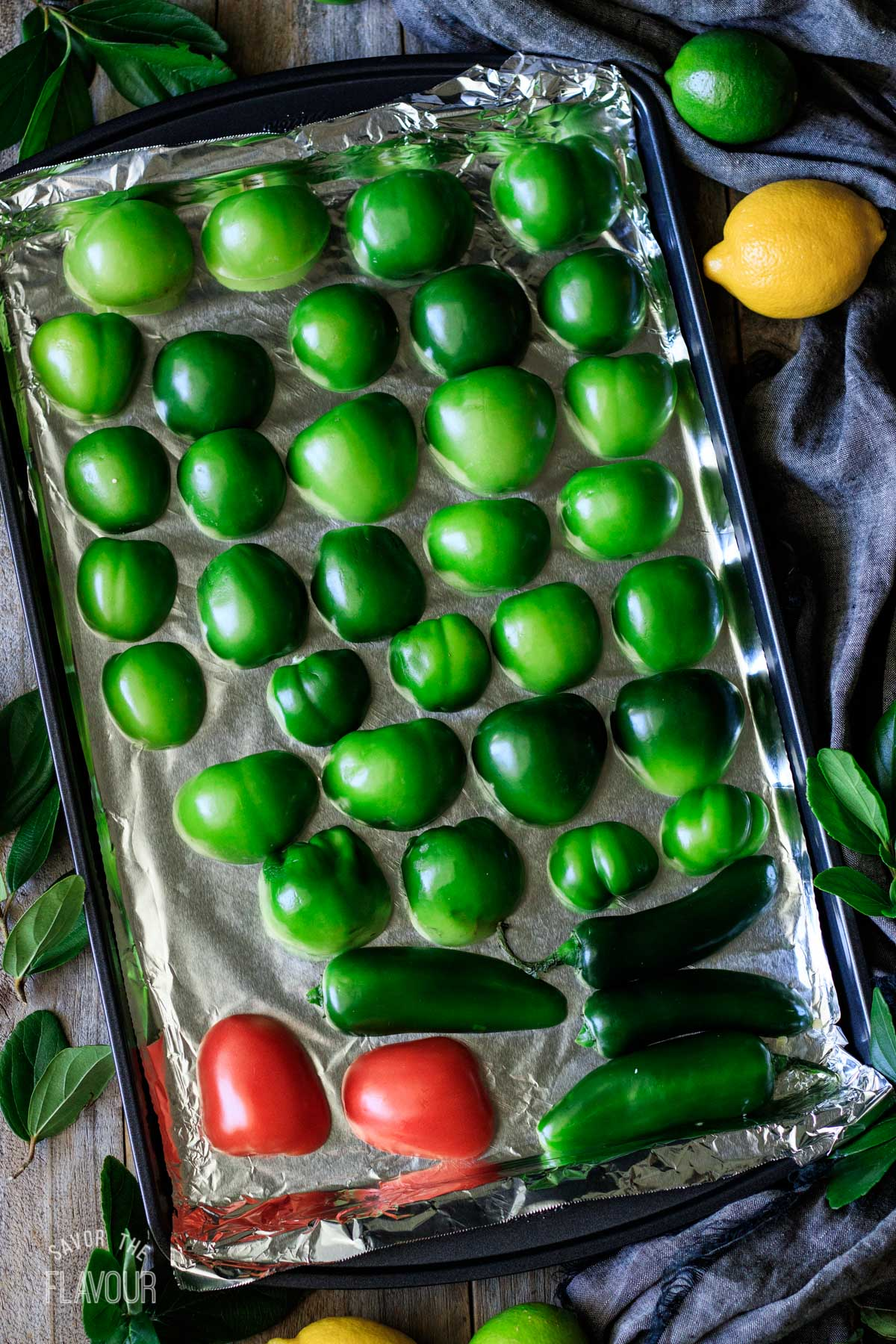halved raw tomatillos, tomato, and jalapenos on a baking tray