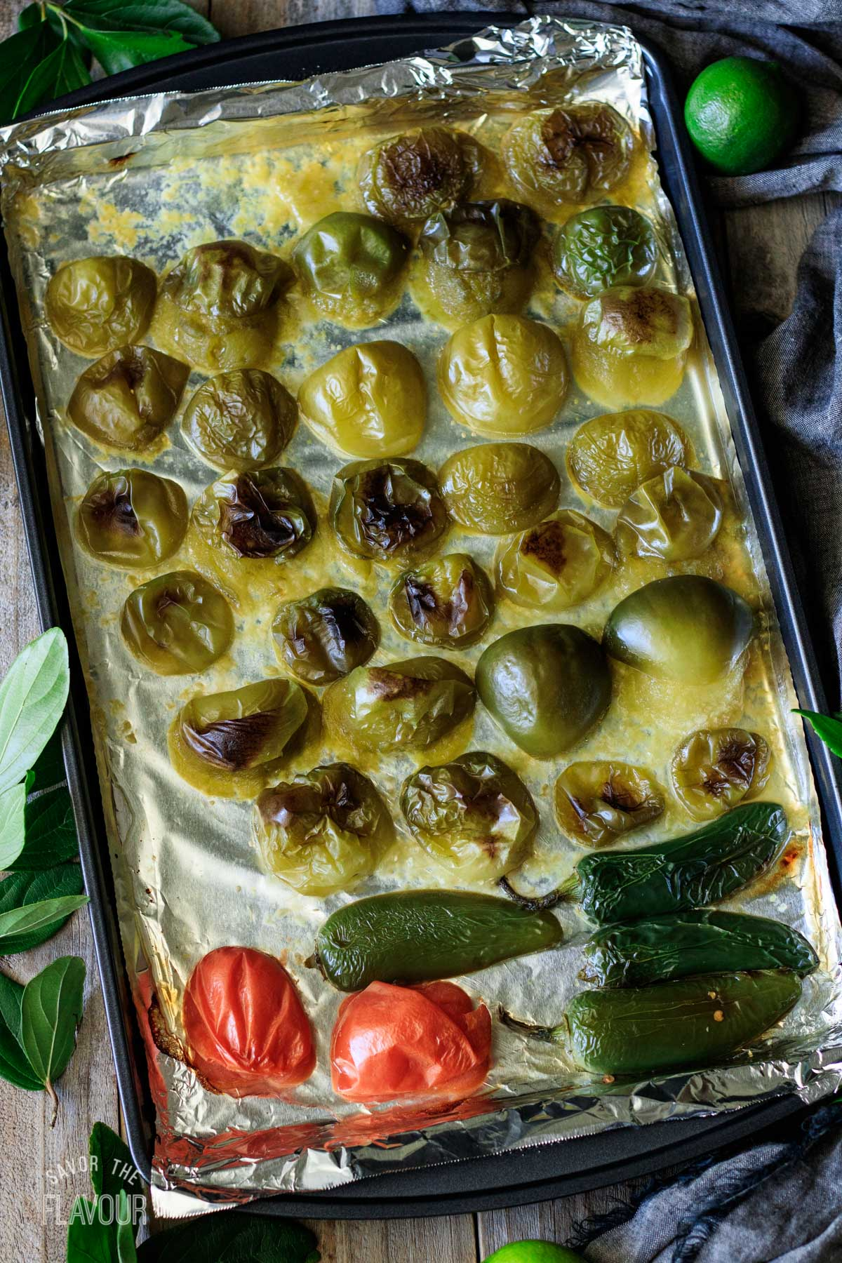 charred tomatillos, tomatoes, and jalapenos on a cookie sheet