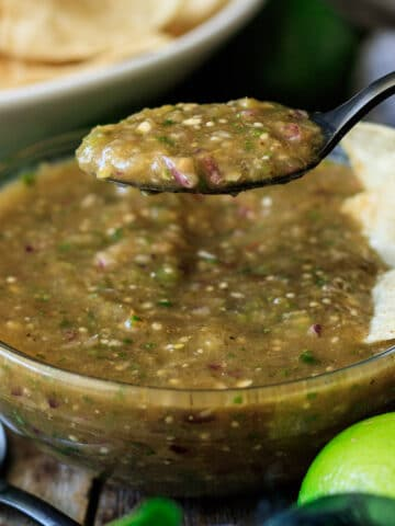 person holding a spoonful of tomatillo salsa