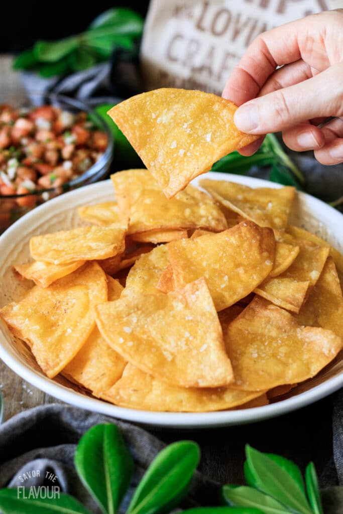person holding a tortilla chip above a bowl of chips
