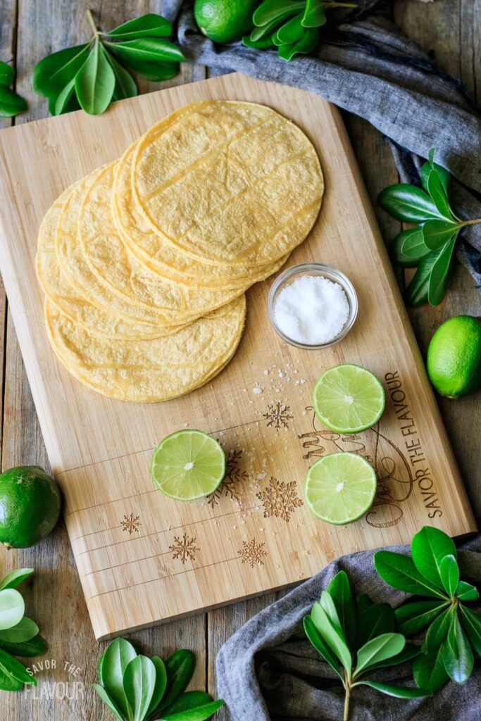 tortillas, salt, and limes on a cutting board
