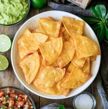 white bowl of tortilla chips with bowls of salsa and guacamole