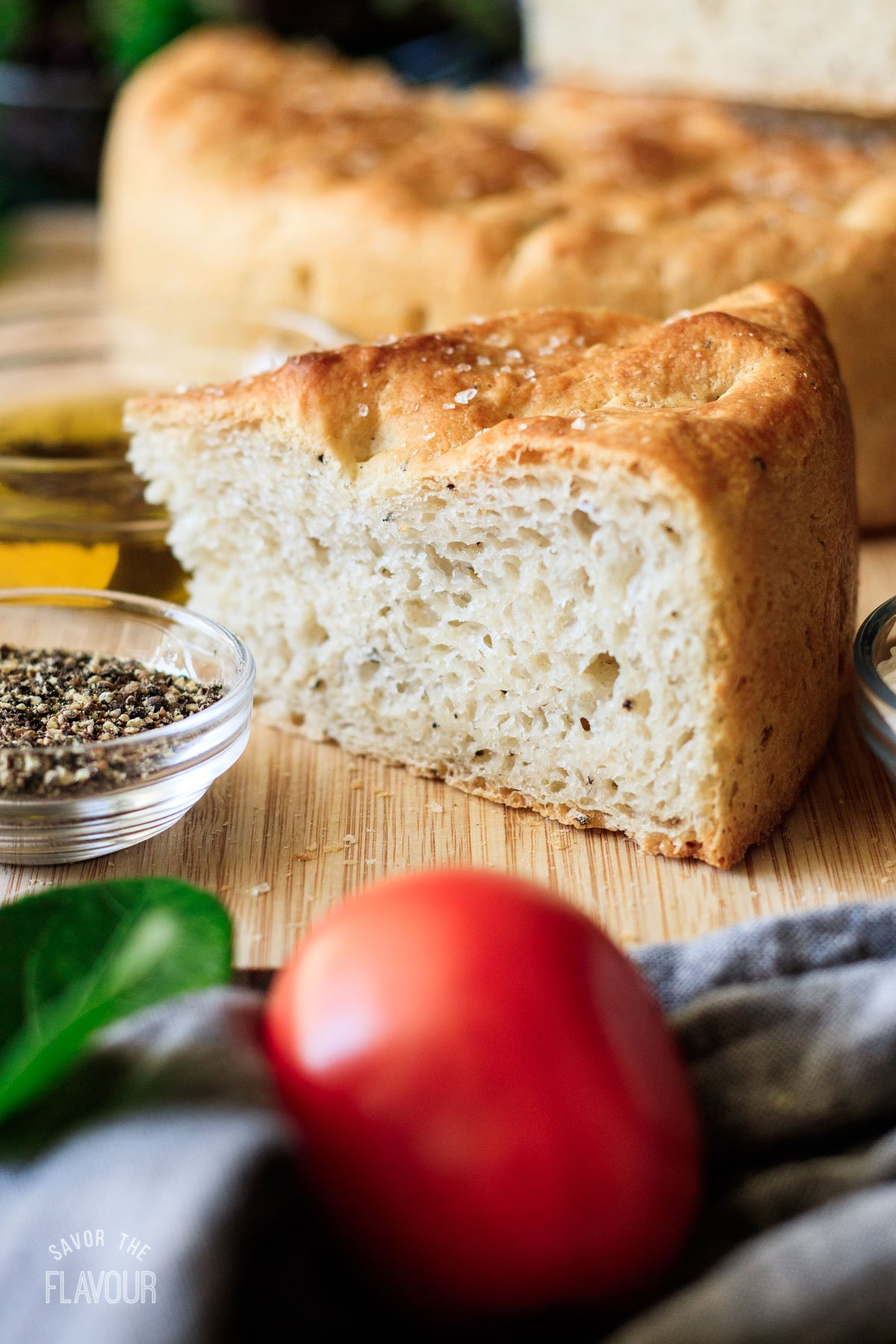 triangular slice of black pepper focaccia with a bowl of olive oil
