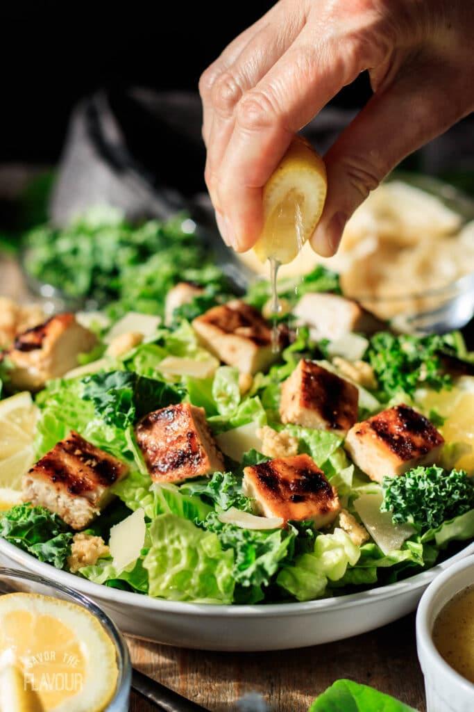 person squeezing a lemon wedge on a lemon kale Caesar salad