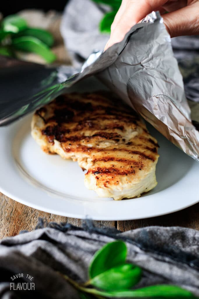 grilled chicken breast on a white plate tented with foil