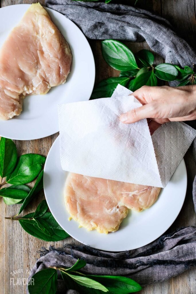person patting chicken breasts dry with paper towel