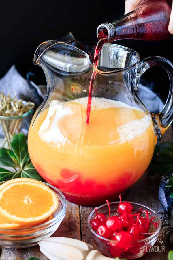 pouring grenadine into a pitcher of fruit juice