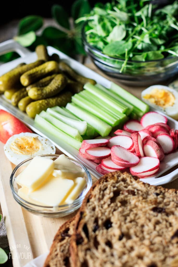 a white plate filled with celery sticks, sliced radishes, and gherkins