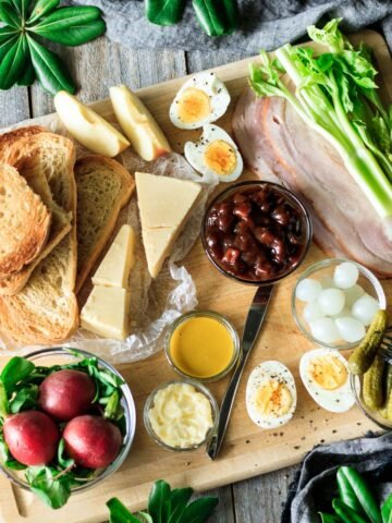ploughman's lunch arranged on a wooden cutting board