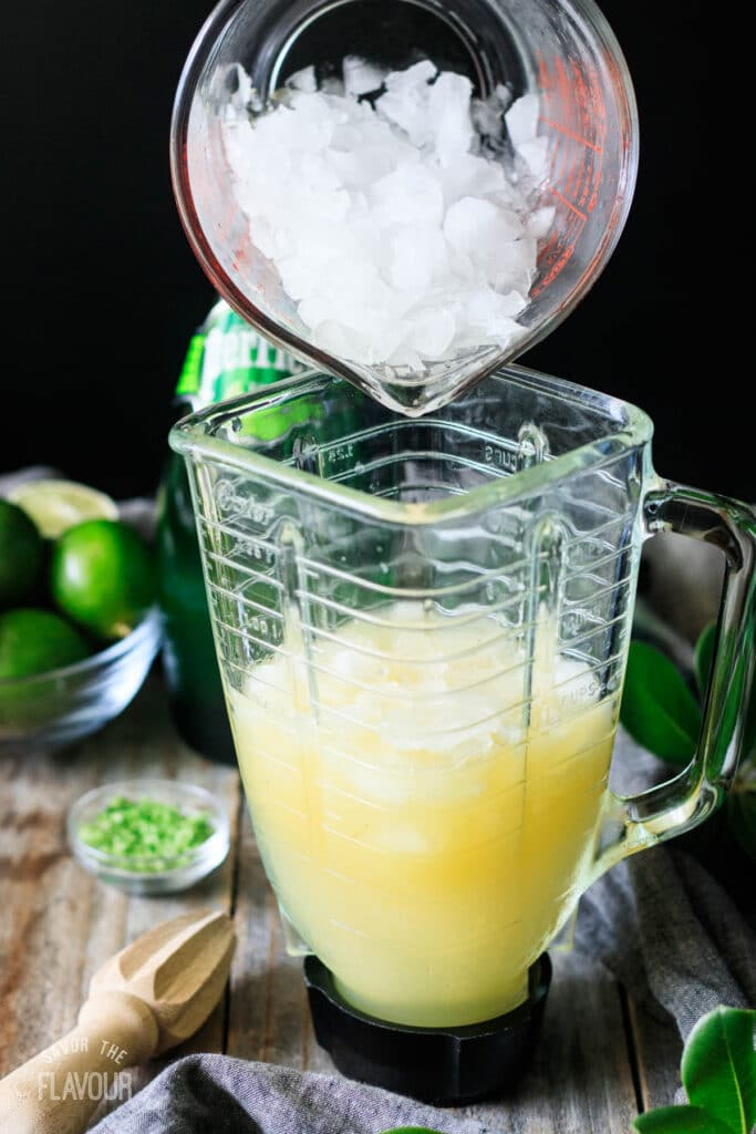 person adding crushed ice to the margarita pitcher