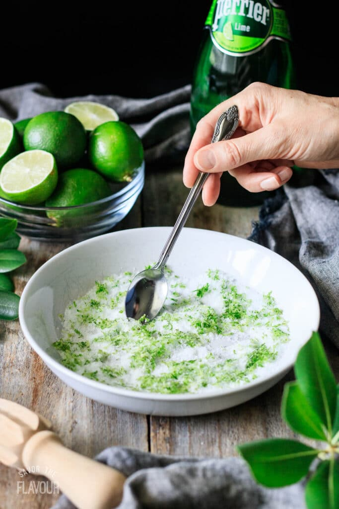 person stirring margarita salt and lime zest together in a white bowl