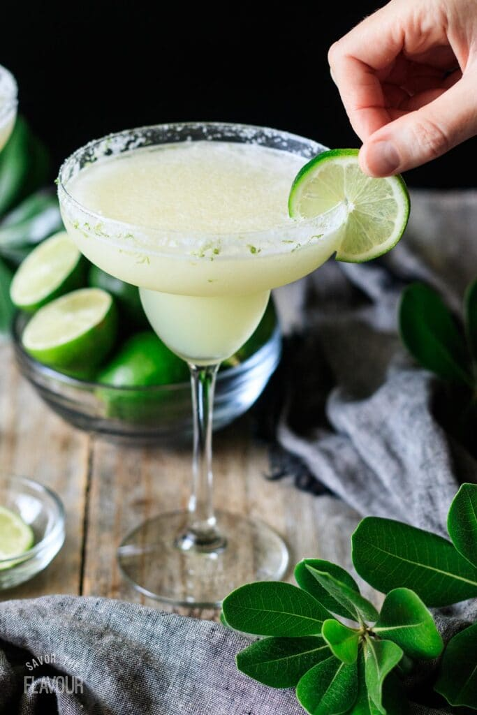 person placing a lime wheel on the rim of a margarita