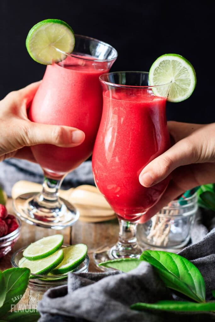 people doing a toast with virgin raspberry daiquiris