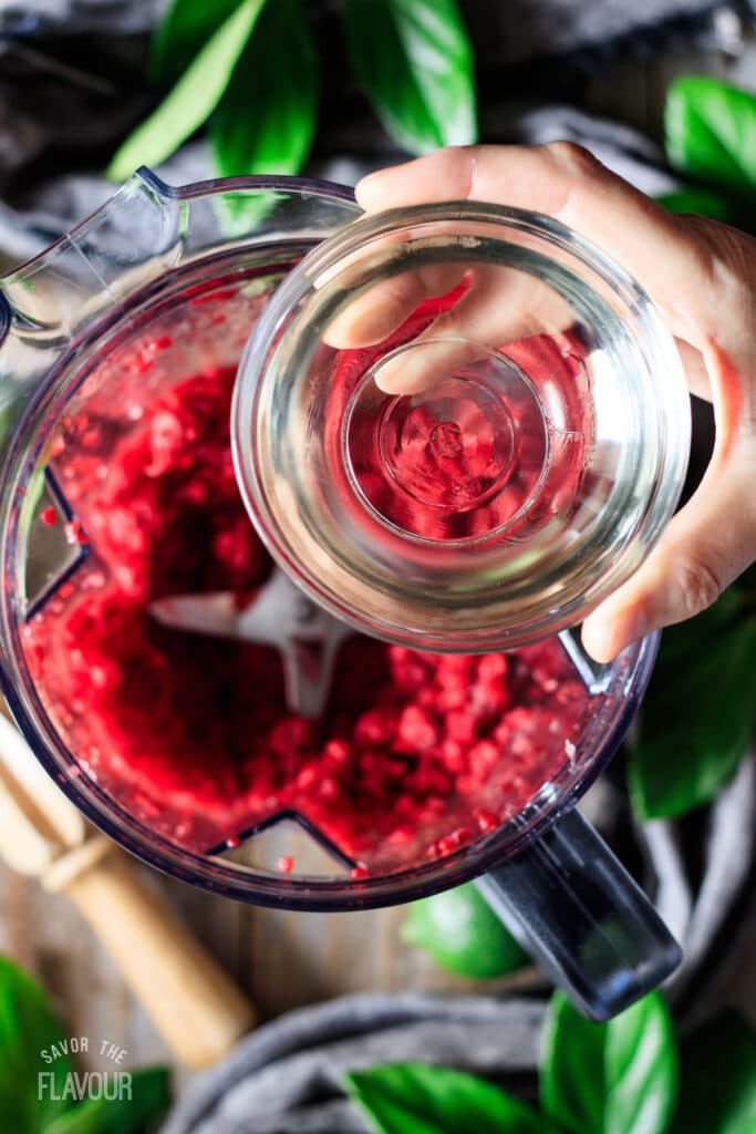 person adding simple syrup to the raspberry mixture