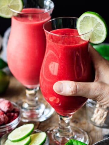person holding a glass of virgin raspberry daiquiri