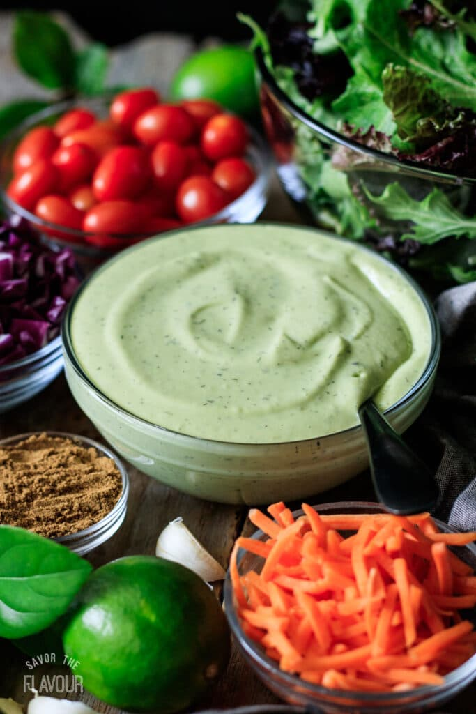 glass bowl of avocado lime ranch with bowls of salad toppings