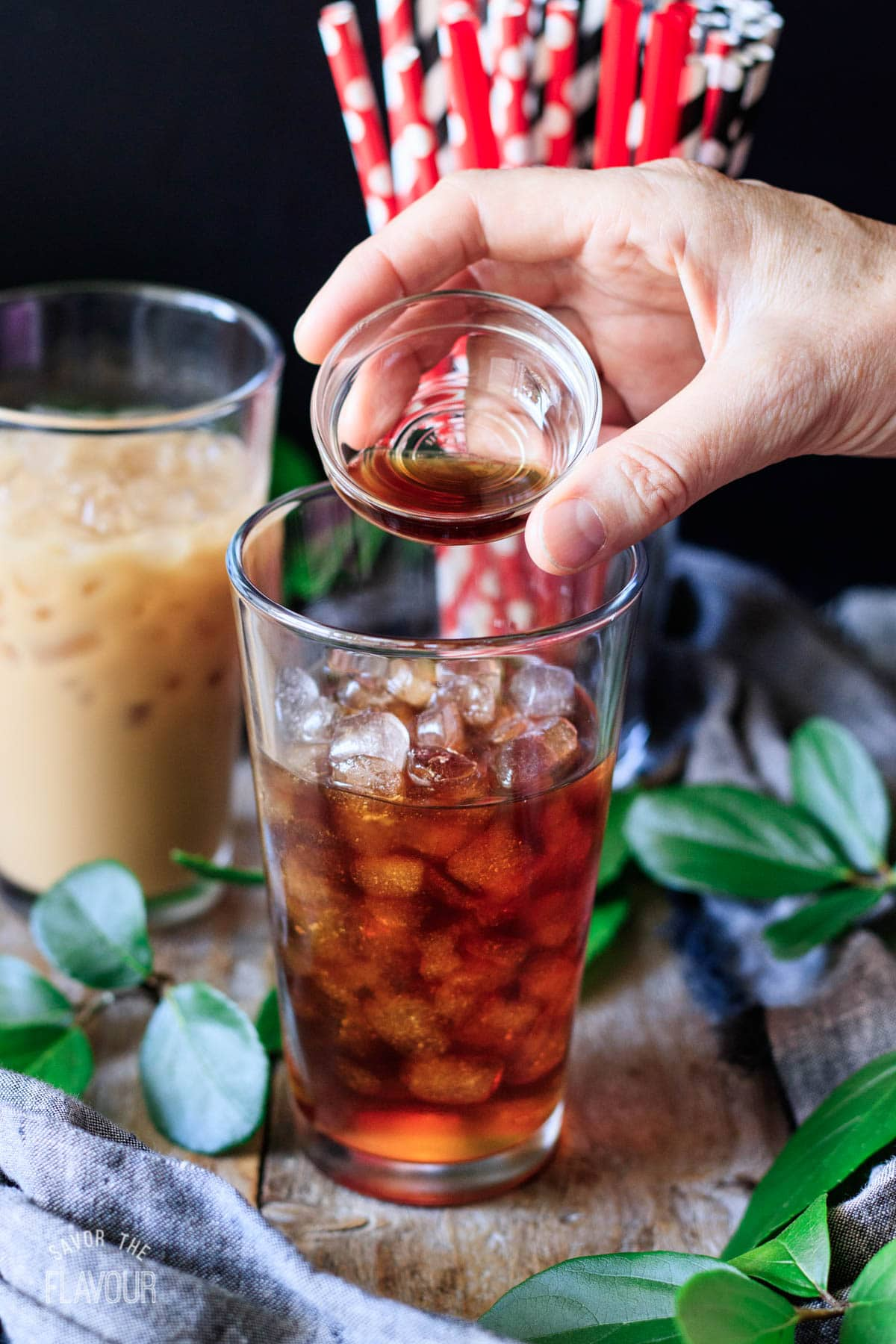 person adding vanilla extract to the iced coffee