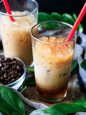 two glasses of Chick-fil-A iced coffee with a bowl of coffee beans