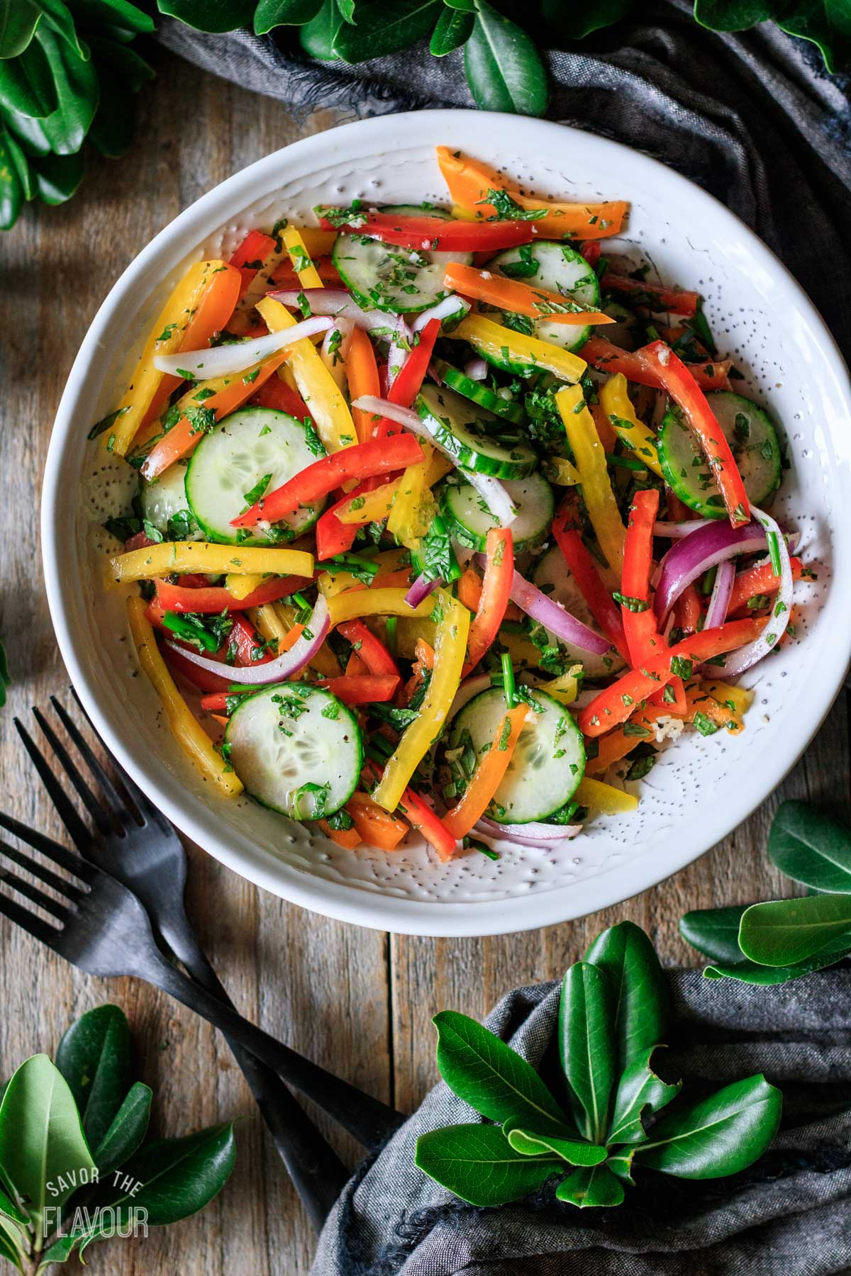 white bowl of bell pepper salad with two forks