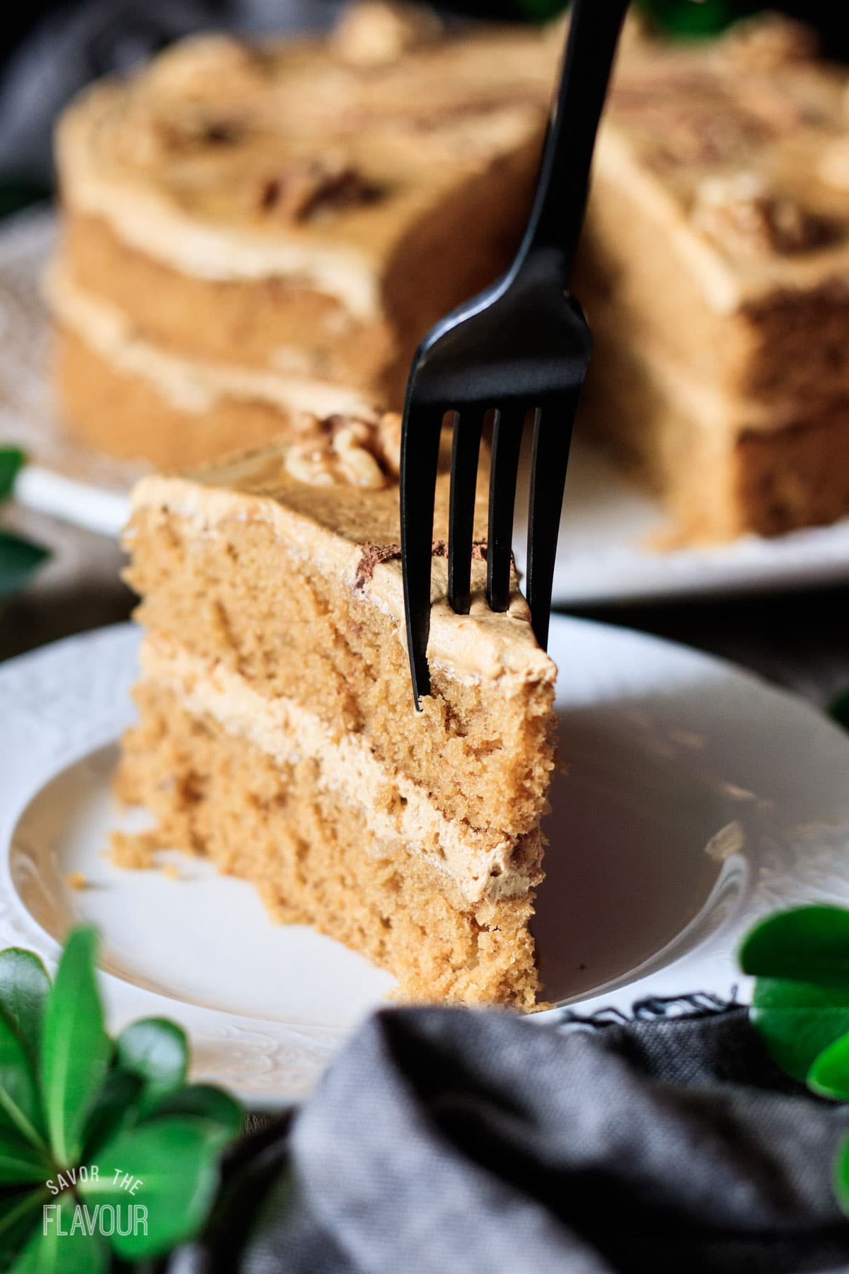 person digging a fork into a slice of coffee walnut cake