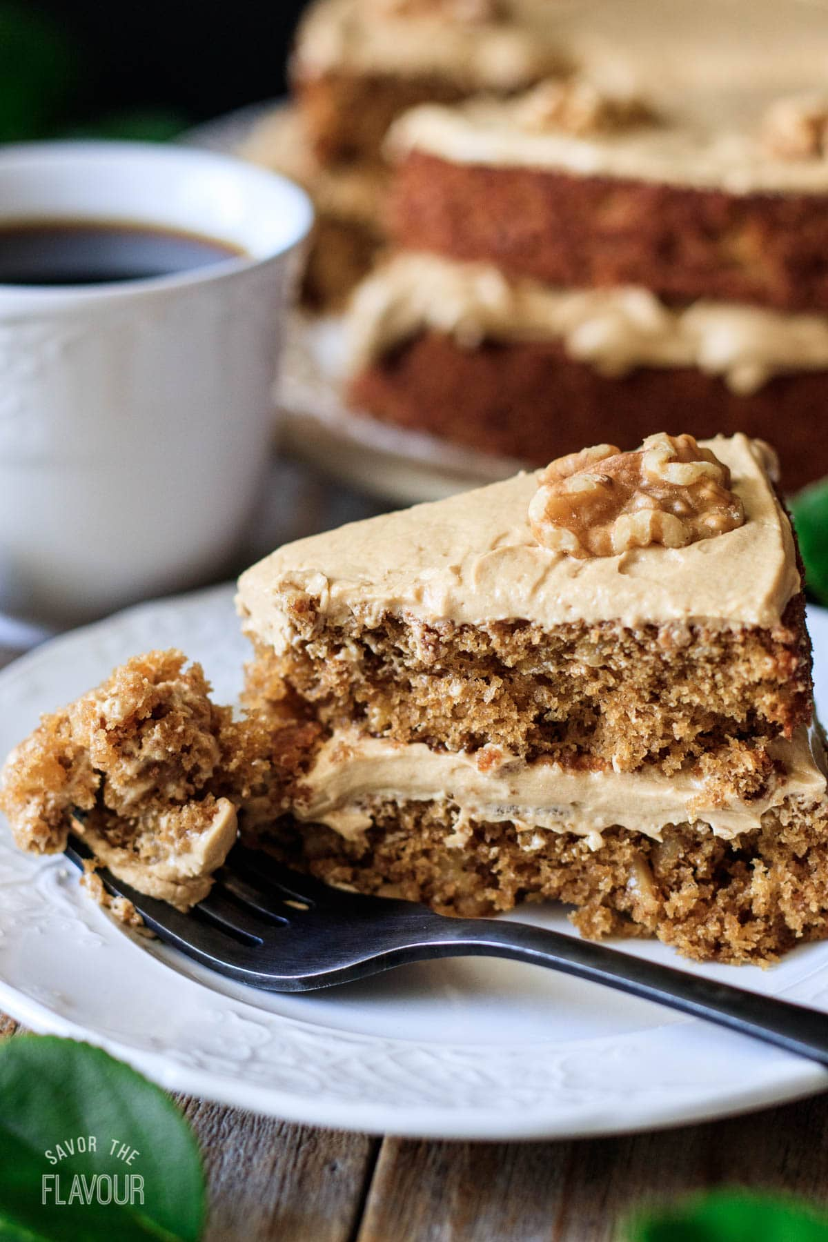 slice of coffee walnut cake on a white plate with a cup of coffee
