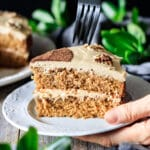 person holding a slice of coffee walnut cake with a fork