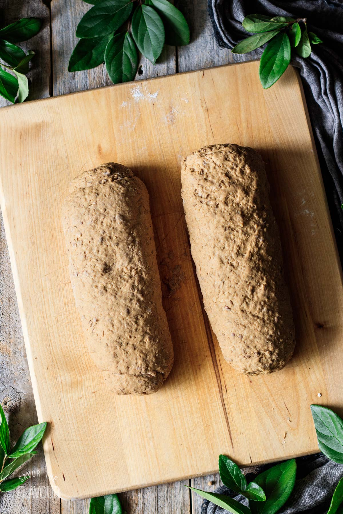 two logs of bread dough on a wooden cutting board