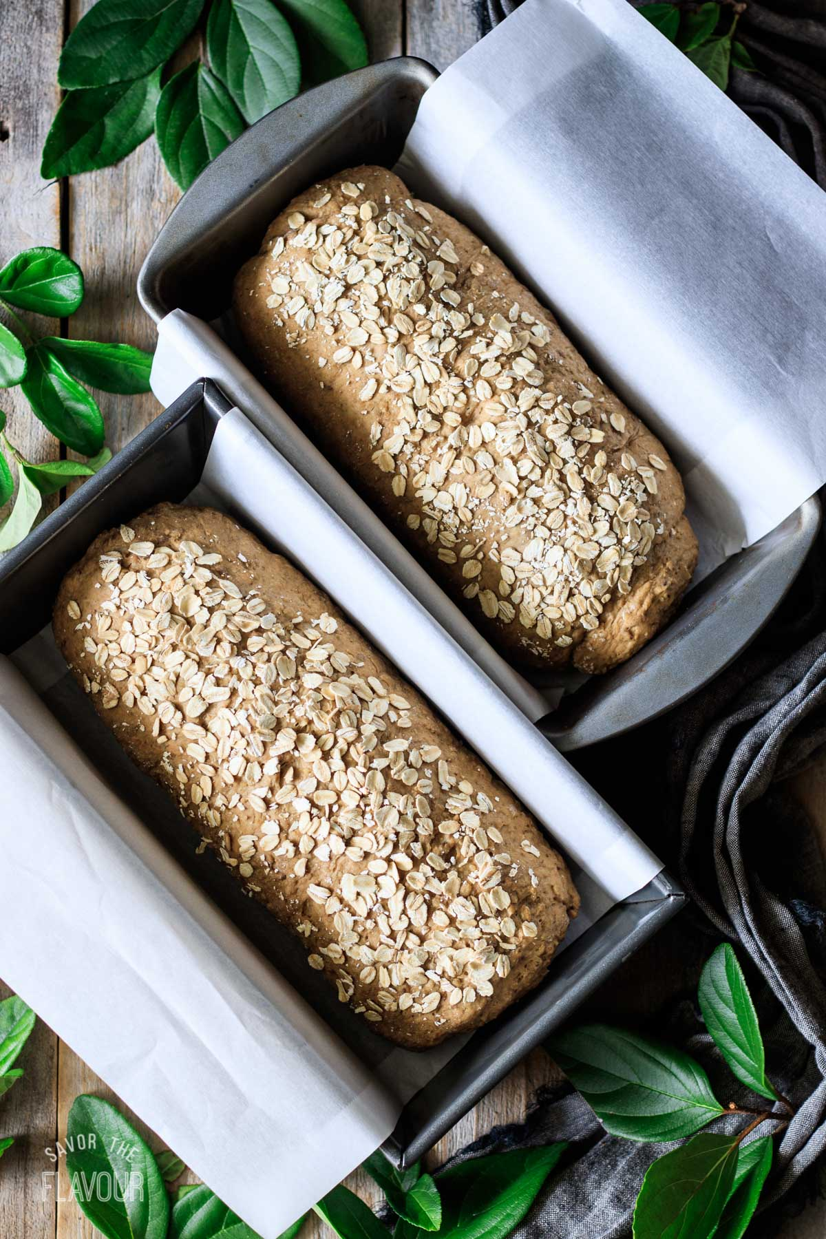 two loaves of bread in parchment-lined loaf pans