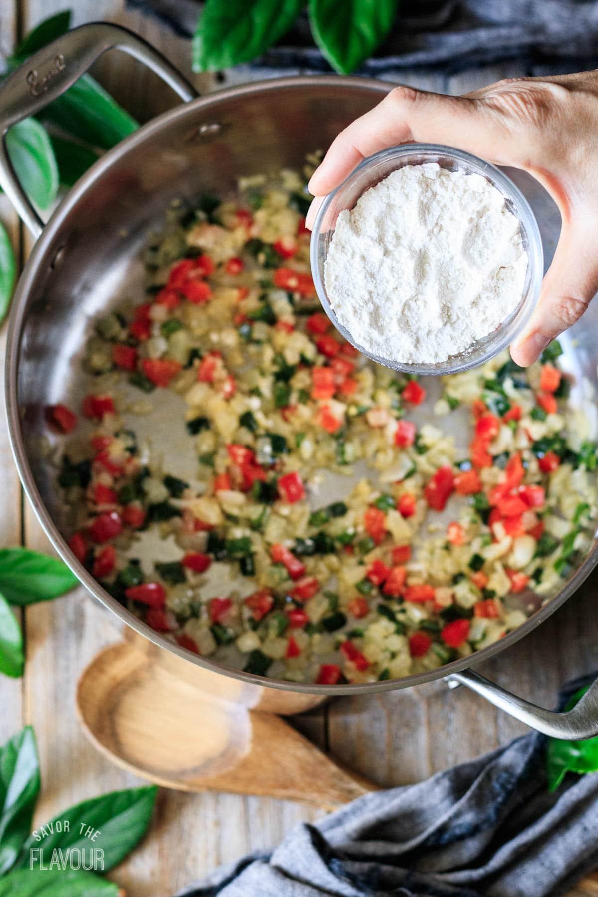 person pouring flour into the pot of sauteed veggies