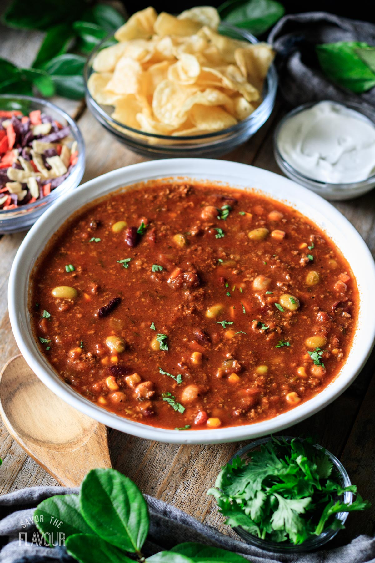 large bowl of Panera turkey chili with bowls of toppings