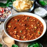 large bowl of Panera turkey chili with a wooden spoon and bowls of toppings