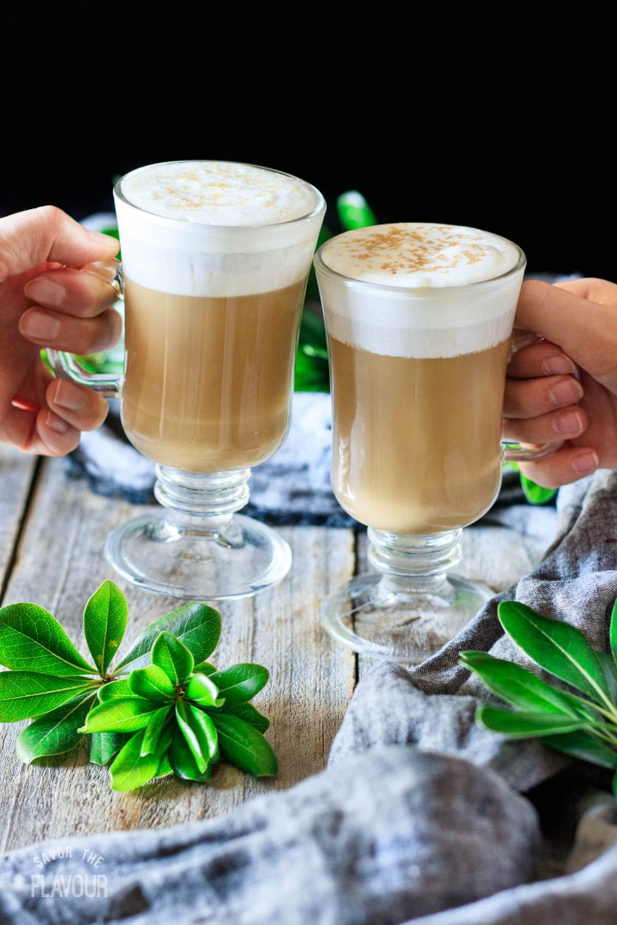 people doing a toast with two smoked butterscotch lattes