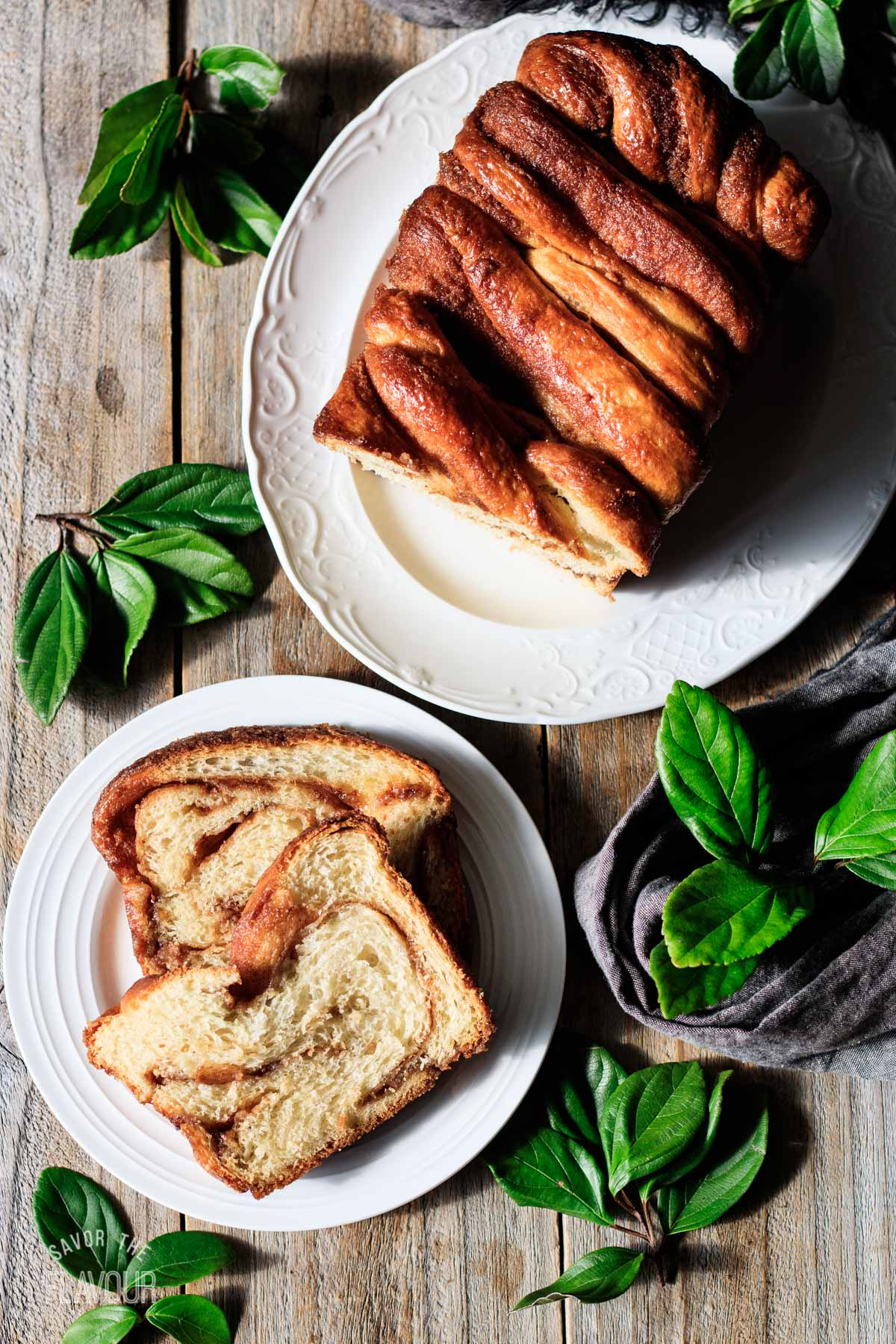 two slices of cinnamon babka on a white plate with the loaf