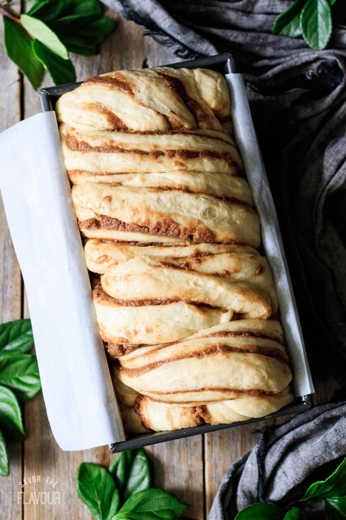 risen babka in a parchment-lined loaf pan