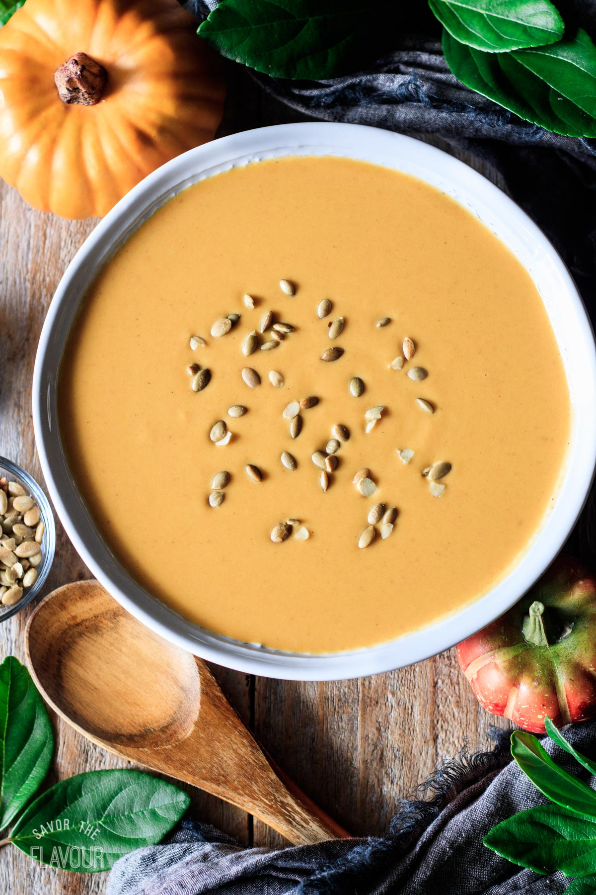 white bowl of Panera autumn squash soup with a wooden spoon