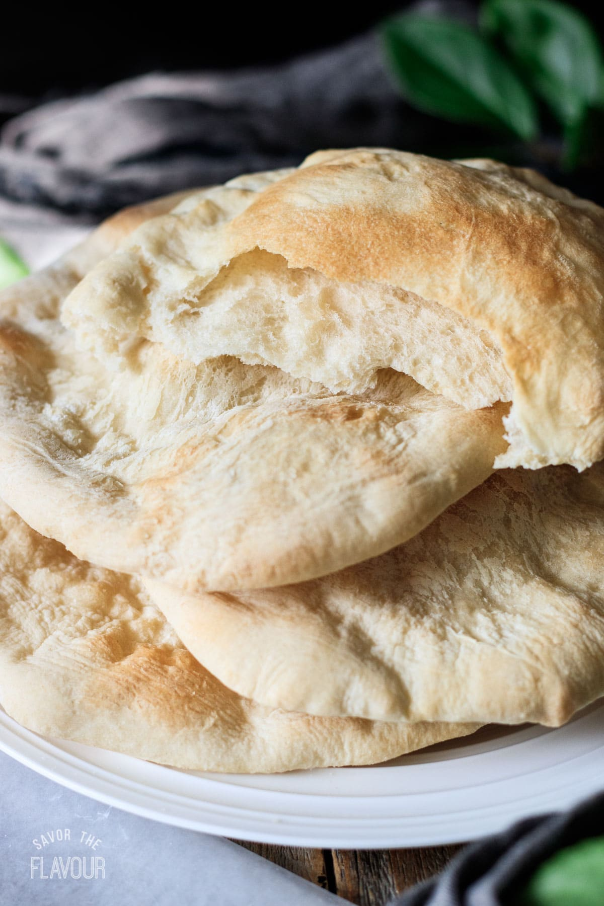 half of a taboon sitting on top of a plate of taboon breads